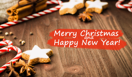 Winter and New Year theme. Spices, cinnamon, anise, cookies in a shape of star, red candies, pepper and gray scarf on wooden background. View from above with text Merry Christmas and Happy New Year. Stock Photo