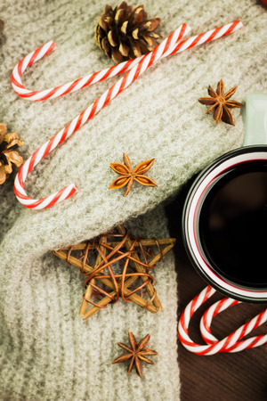 Christmas hot steaming cup of glint wine with spices, anise, fir cones, cookies in a shape of star, red candies, pepper and gray scarf on wooden background. View from above. Flat lay.