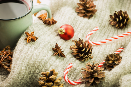 Winter and New Year theme. Christmas hot steaming cup of glint wine with spices, anise, fir cones, cookies in a shape of star, red candies, fir cones, pepper and gray scarf on wooden background.