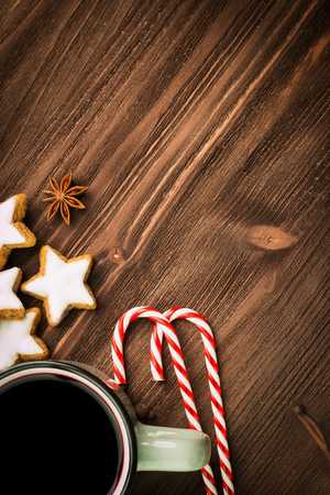 Christmas hot steaming cup of glint wine with spices, anise, cookies in a shape of star, red candies, pepper on wooden background. Copy space for text. View from above. Flat lay.
