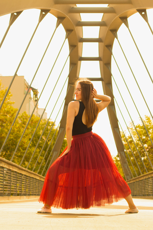 Young slim beautiful woman with long brown hair dancing and smiling outdoors in black shirt and terracotta (red pear) long skirt. Sport and healthy conсept. 写真素材 - 112679830