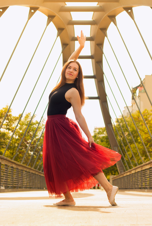 Young slim beautiful woman with long brown hair dancing and smiling outdoors in black shirt and terracotta (red pear) long skirt. Sport and healthy con�ept.