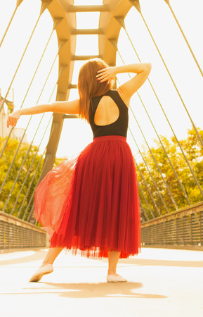 Young slim beautiful woman with long brown hair dancing outdoors in black shirt and terracotta (red pear) long skirt. Turning back.  Sport and healthy conсept.