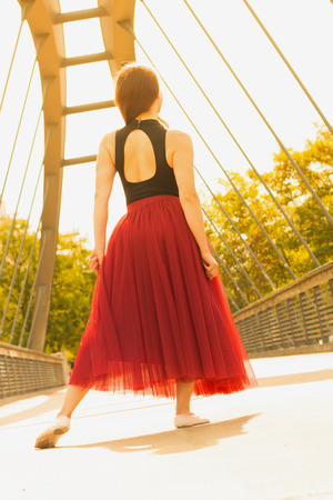 Young slim beautiful woman with long brown hair dancing outdoors in black shirt and terracotta (red pear) long skirt. Turning back.  Sport and healthy con�ept.