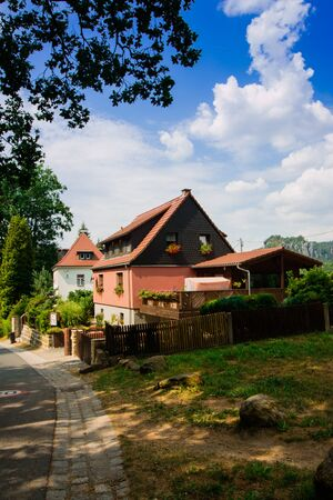 Rathen, Germany - August 4th, 2018: Rathen, Saxon Switzerland National Park. View of german houses on blue sky background with clouds. Road leading to Bastei Bridge. 版權商用圖片 - 142313898