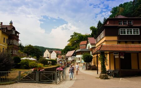 Rathen, Germany - August 4th, 2018: Rathen, Saxon Switzerland National Park. View of german houses on blue sky background with clouds. Road leading to Bastei Bridge. 版權商用圖片 - 142313901