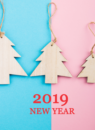 Christmas and New Year's Day festive decoration, wooden Christmas tree on blue and pink background.  Copy space for text. Flat lay. View from above with text 2019 New Year.