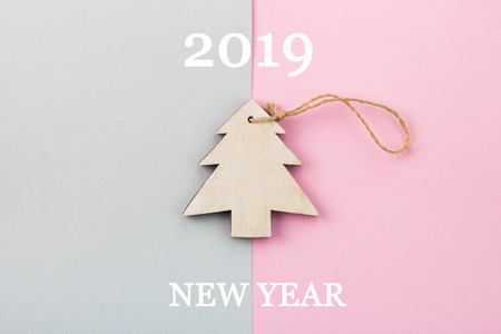 Christmas and New Year's Day festive decoration, wooden Christmas tree on pink and gray background.  Copy space for text. Flat lay. View from above with text 2019 New Year. Stock Photo