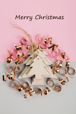 Christmas and New Year's Day festive decoration, wooden Christmas tree with golden ribbons on pink and gray background.  Copy space for text. Flat lay. View from above with text Merry Christmas.