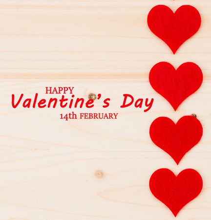 St.Valentine's Day holiday background. Red hearts in a shape of a heart on wooden background. Flat lay. View from above with text Happy Valentine's Day and 14th February.