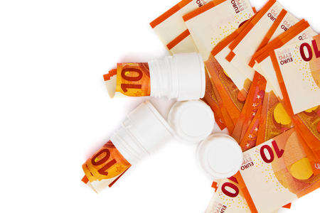 Symbolic picture for high cost of medicine with pill bottle on money (10 euro banknotes). Rolled euro banknotes in white pill bottle. Medical concept. Copy space for text. Top view.