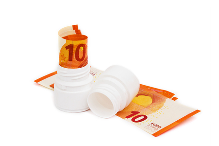 Symbolic picture for high cost of medicine with pill bottle on money (10 euro banknotes). Rolled euro banknotes in white pill bottle. Medical concept. Copy space for text. Stok Fotoğraf