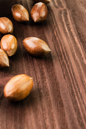 Pecan nuts in the shell on wooden background. The concept of proper nutrition, vitamins and minerals, antioxidants. Copy space for text. Banco de Imagens