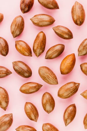 Not cleaned pecan nuts in the shell on pink background. The concept of useful foods and proper nutrition, natural vitamins and minerals, antioxidants. Top view. Flat lay. Banco de Imagens