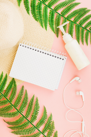 Summer, travel, vacation concept flat lay. Beach accessories: sunscreen lotion, notebook, summer hat,  fern and white headphones on pink background. Top view. Space for text. Stok Fotoğraf