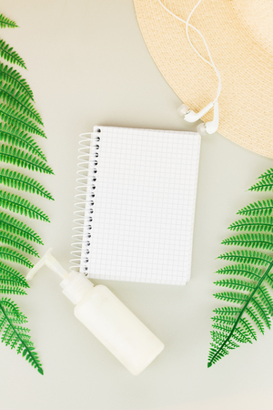 Summer, travel, vacation concept flat lay. Beach accessories: sunscreen lotion, notebook, summer hat,  fern and white headphones on gray background. Top view. Space for text. Stock Photo