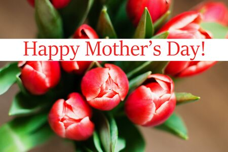 Spring theme. Mothers Day festive background. The bouquet of red tulips on brown background. Close up. Top view with text Happy Mothers Day.