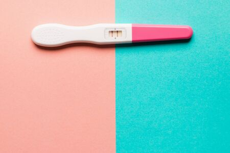 Positive pink plastic pregnancy test on pink and blue background. Top view. Flat lay. Copy space for text. Stock Photo