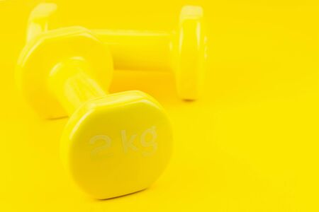 Sport background. Yellow dumbbells on yellow background. Still life and health care concept. View from above. Copy space for text. Stock Photo