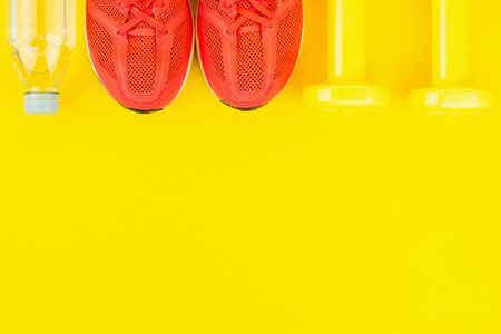 Sport background. Yellow dumbbells, a bottle of fresh water and pink sneakers on yellow background. Still life and health care concept. Flat lay, view from above. Copy space for text.