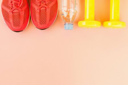 Sport background. Yellow dumbbells, a bottle of fresh water and pink sneakers on pink background. Still life and health care concept. Flat lay, view from above. Copy space for text.
