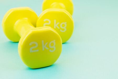 Sport background. Yellow dumbbells on blue background. Still life and health care concept. View from above. Copy space for text.