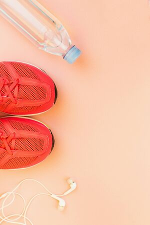 Sport background. White headphones, a bottle of fresh water and pink sneakers on pink background. Still life and health care concept. Flat lay, view from above. Copy space for text.