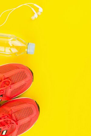 Sport background. White headphones, a bottle of fresh water and pink sneakers on yellow background. Still life and health care concept. Flat lay, view from above. Copy space for text.