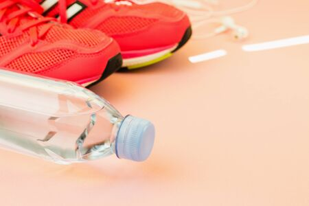 Sport background. White headphones, a bottle of fresh water and pink sneakers on pink background. Still life and health care concept. View from above. Copy space for text. Stock Photo