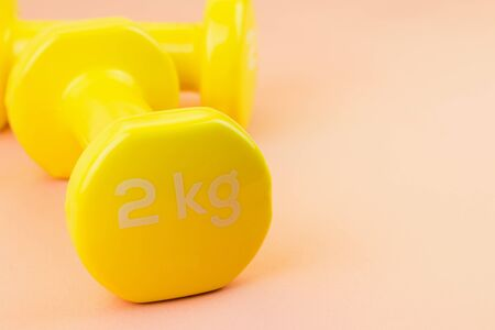 Sport background. Yellow dumbbells on pink background. Still life and health care concept. View from above. Copy space for text.