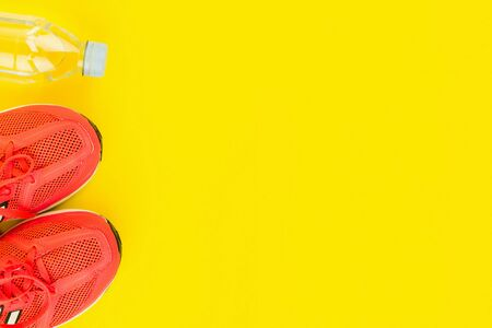 Sport background. Bottle of fresh water and pink sneakers on yellow background. Still life and health care concept. Flat lay, view from above. Copy space for text. Stock Photo