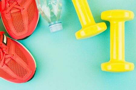 Sport background. Yellow dumbbells, a bottle of fresh water and pink sneakers on blue background. Still life and health care concept. Flat lay, view from above. Copy space for text. Stock Photo