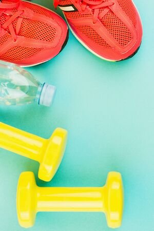 Sport background. Yellow dumbbells, a bottle of fresh water and pink sneakers on blue background. Still life and health care concept. Flat lay, view from above. Copy space for text. Imagens