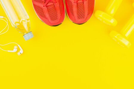 Sport background. White headphones, yellow dumbbells, a bottle of fresh water and pink sneakers on yellow background. Still life and health care concept. Flat lay, view from above. Copy space for text.