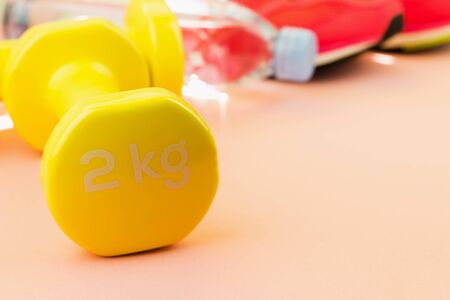Sport background. Yellow dumbbells, a bottle of fresh water and pink sneakers on pink background. Still life and health care concept. View from above. Copy space for text.