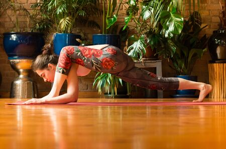 Young woman practicing yoga in studio. Sitting on red yoga mat and meditating, stretching. Loft and stylish interior (wooden floor and brick wall). Healthy and sport concept. 版權商用圖片