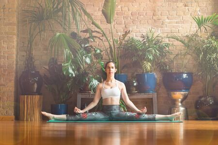 Young woman practicing yoga in studio. Sitting on green mat and meditating, holding hands on both sides, making split. Loft interior with wooden floor and brick walls. Healthy and sport concept.