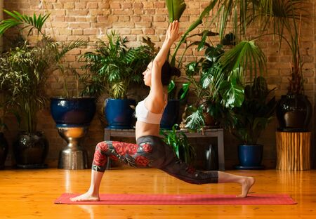 Young woman practicing yoga in studio. Staying on red mat and meditating, holding hands together, making split. Loft interior with wooden floor and brick walls. Healthy and sport concept. 版權商用圖片