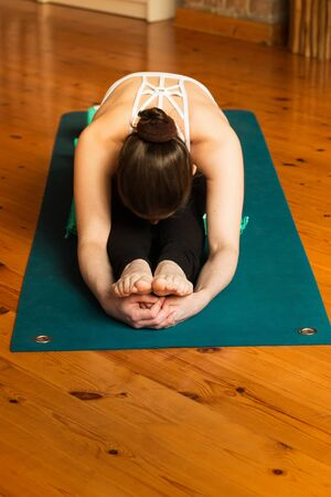 Young woman practicing yoga in studio. Sitting on green yoga mat and meditating. Loft and stylish interior (wooden floor and brick wall). Healthy and sport concept.
