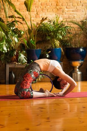 Young woman practicing yoga in studio. Sitting on red yoga mat and stretching with yoga ring. Loft and stylish interior (wooden floor and brick wall). Healthy and sport concept. 版權商用圖片