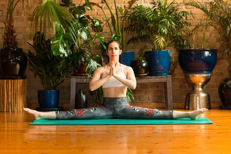 Young woman practicing yoga in studio. Sitting on green mat and meditating, holding hands together, making split. Loft interior with wooden floor and brick walls. Healthy and sport concept. 版權商用圖片