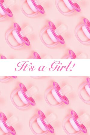 Pattern pink baby pacifiers, dummy with rubber nipple on pink background with text it's a girl. Flat lay. Top view.