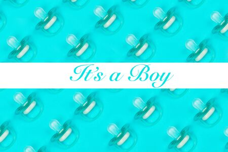 Pattern blue baby pacifiers, dummy with rubber nipple on blue background with text Its a boy. Flat lay. Top view.