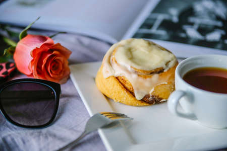 french ethnicity: bun with cinnamon and kremoi on a pink plate in a romantic setting with roses