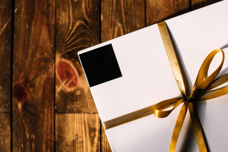 textile image: White Gift Box with Yellow Gold Ribbon Isolated