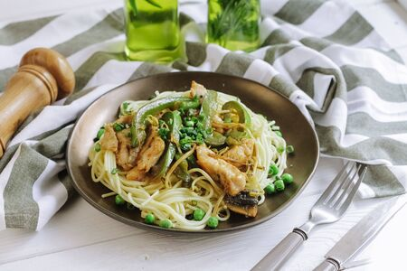 home cooked pasta spaghetti with grilled chicken breast and green bell pepper, peas and green onion and olive oil