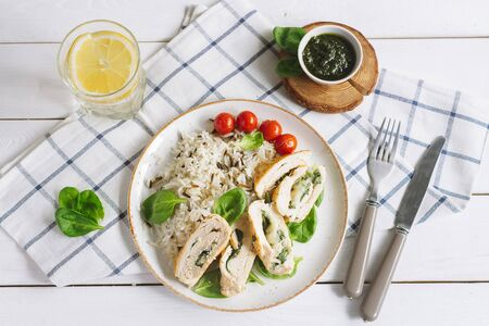 Chicken fillet roll with spinach. Garnished with long-grain wild rice. Cherry tomatoes, pesto sauce, a glass of water and a slice of lemon. Checkered cloth, knife and fork. On a white wooden table. Stock Photo