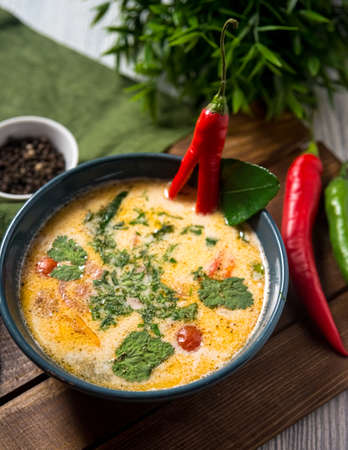 Tom yum soup portion in a blue bowl on a wooden board and table. Slightly above view. Decorated with hot pepper and herb leaves. Green table cloth and a spoon on a side.