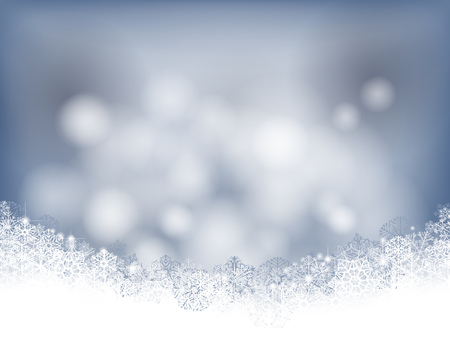 Winter background. Wave border made of fluffy snowflakes with space for text on soft bluebokeh  background.