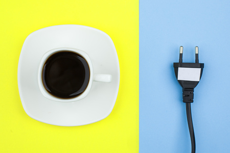 Trendy flat lay minimal concept, unplugged cord and cup of coffee n bright background, concept of a break, rest from modern technologies